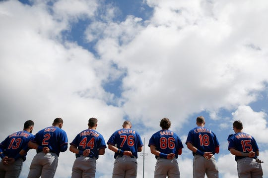 The New York Mets observe the playing of the national anthem prior to a Grapefruit League spring training game against the St. Louis Cardinals at Roger Dean Stadium on February 22, 2020 in Jupiter, Florida.