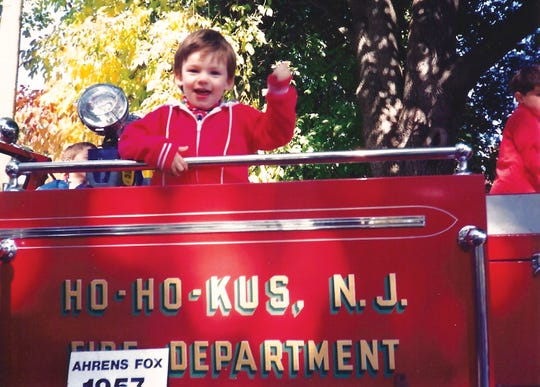 Kevan Kenney poses outside of his childhood home on a Ho-Ho-Kus firetruck