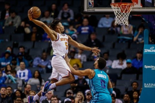 New York Knicks guard Dennis Smith Jr. drives for a dunk over Charlotte Hornets forward Miles Bridges during the first half of an NBA basketball game in Charlotte, N.C., Wednesday, Feb. 26, 2020.
