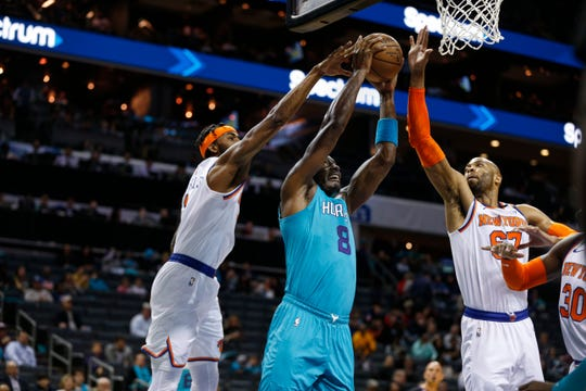 Charlotte Hornets center Bismack Biyombo, center, goes up for a dunk between New York Knicks forward Maurice Harkless, left, and center Taj Gibson during the first half of an NBA basketball game in Charlotte, N.C., Wednesday, Feb. 26, 2020.