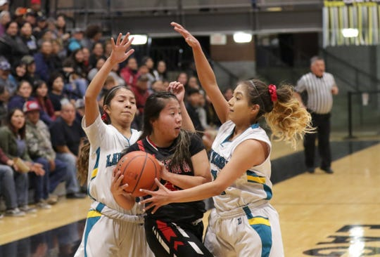 Navajo Prep's Cienna Harrison (10) and Laila Charley (1) trap Crownpoint's Amaya McMillan near the outer baseline during Wednesday's District 1-3A girls basketball tournament semifinals game at the Eagles Nest in Farmington.
