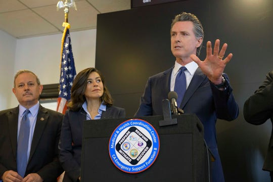 California Governor Gavin Newsom speaks to members of the press at a news conference in Sacramento, Calif., Thursday, Feb. 27, 2020. Newsom spoke about the state's response to novel coronavirus, also known as COVID-19. Behind him are Director of the Governor's Office of Emergency Services Mark Ghilarducci, right, and California Department of Public Health Director and State Health Officer Dr. Sonia Angell. Yesterday, the Centers for Disease Control and Prevention confirmed a possible first case of person-to-person transmission of COVID-19 in California in the general public.(AP Photo/Randall Benton)