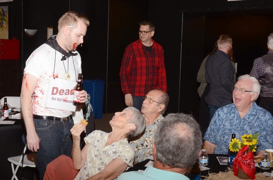"""From DTW's 2019 fundraiser: A guest asks a """"dead"""" character a question in an attempt to figure out whodunnit."""