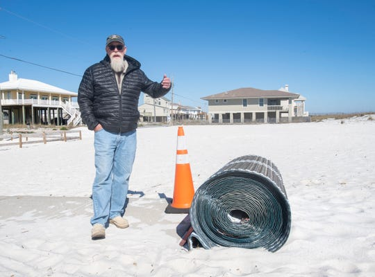 Steve Luppert, a retired National Parks Service facilities manager and beachside resident, talks about the negative aspects of Mobi-Mats while standing near the rolled up mat at walkover number 25A along Pensacola Beach on Thursday, Feb. 27, 2020.