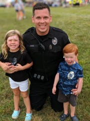 Officer Frank Jones poses with his daughter Leah and son Noah at a National Night Out event.