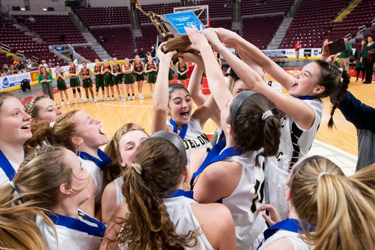 The Delone Catholic Squirettes celebrate with the District 3 Class 3A trophy after defeating Trinity 44-22 in the Giant Center in Hershey on Thursday, Feb. 27, 2020. It was the Squirettes first district title since 2004.