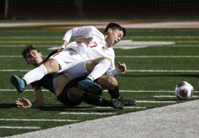 Brophy Prep's Charlie Cobb (left) tackles Chaparral's Blake Bernal (7) during the Class 6A boys state soccer championship game Feb. 26, 2020.