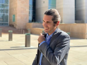 Scott Warren smiles outside the Tucson federal courthouse on Feb. 27, 2020, after a judge tossed out a conviction against him on a misdemeanor charge related to humanitarian aid activities along the U.S.-Mexico border.