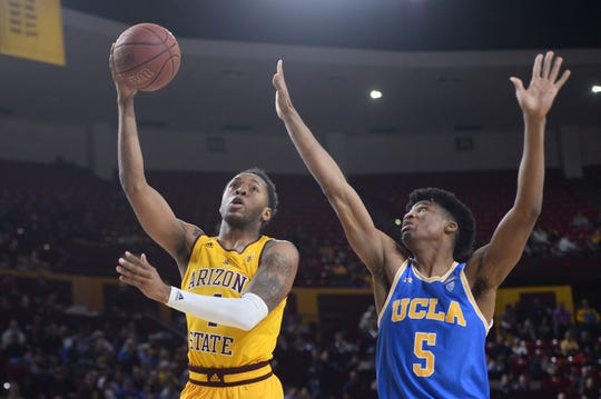 Arizona State Sun Devils forward Kimani Lawrence (4) puts up a layup over UCLA Bruins guard Chris Smith (5) during the second half at Desert Financial Arena. ASU and UCLA face off on Thursday night in an important Pac-12 Conference showdown.