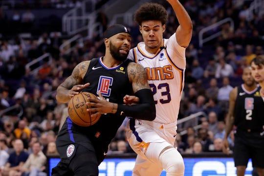 Los Angeles Clippers forward Marcus Morris Sr. drives as Phoenix Suns forward Cameron Johnson (23) defends during the first half of an NBA basketball game, Wednesday, Feb. 26, 2020, in Phoenix. (AP Photo/Matt York)