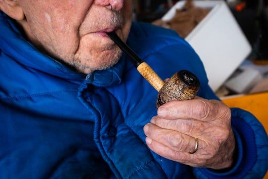 Luthard Eid, 103, sits in a chair in the garage of his Port Huron home, smoking his pipe, Thursday, Feb. 27, 2020. Eid, who is turning 104 on Saturday, says smoking a pipe instead of cigars has helped him live a long life.