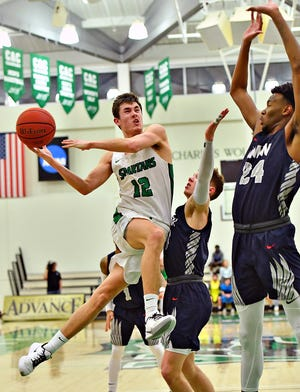York College men's basketball player Logan Collins, left, takes the ball to the hoop in a file photo from Feb. 26, 2020. The Spartans were scheduled to compete in their first Middle Atlantic Conference athletic season in 2020-2021. Those plans have been derailed by the pandemic. The MAC has announced it will move forward with shortened and delayed basketball seasons starting Feb. 11. York, however, has opted not to compete in those seasons.