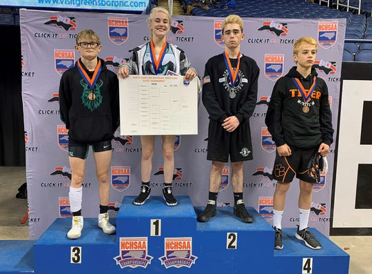 This photo provided by North Carolina High School Athletic Association (NCHSAA) shows Heaven Fitch, center, Luke Wilson, left, and Hunter Fulp, right, and Brandon Ropp, far right,  after the state wrestling championships in Raleigh, N.C, on Saturday, Feb. 22, 2020.  NCHSAA said on its website that Fitch of Uwharrie Charter became the first female to win one of the association's individual state wrestling championships. She won the 106 pound (48 kg) weight class at the 1A division on Saturday.  (North Carolina High School Athletic Association via AP)