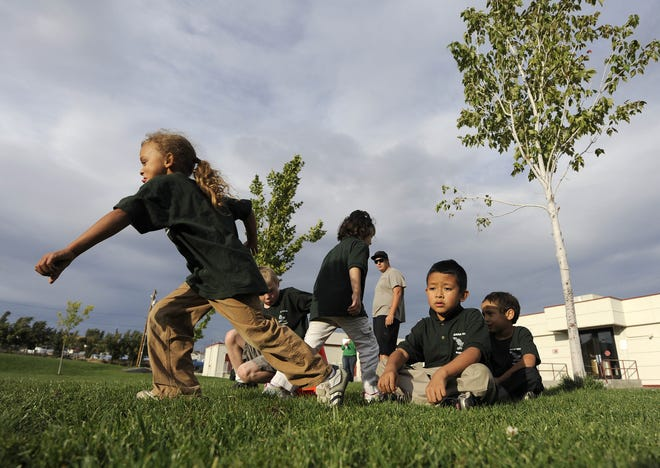 Fees for after-school care may be going up in Reno because of an increase in the mandated minimum wage. Kindergarten and second-grade students run races during the after-school program in this file photo.