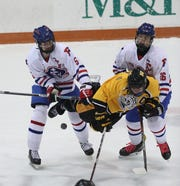McQuaid's Aiden Nasca is checked off the puck by Fairport's Sam Hoyen (5) and Nick Krug (26).