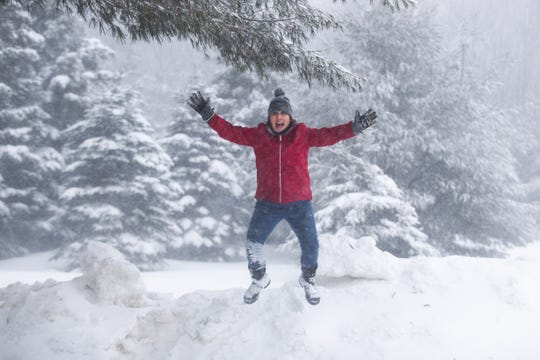 Carolyn Yerdon, a weather observer for the National Weather Service and a resident of North Redfield, jumps off a snowbank in her backyard on Thursday, Feb. 27, 2020. Yerdon is passionate about sharing snowfall totals on social media and often shares photos of herself in the snow to illustrate snow totals.