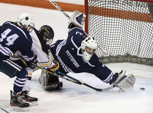 Victor's Alex Parton pushes the puck just out of the reach of Pittsford goalie Alex Tidd for a first period goal.  Victor went on to win 3-0 in the Class A semifinal game.