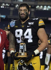 A.J. Epenesa holds the most valuable defensive player trophy after the Holiday Bowl against Southern California.