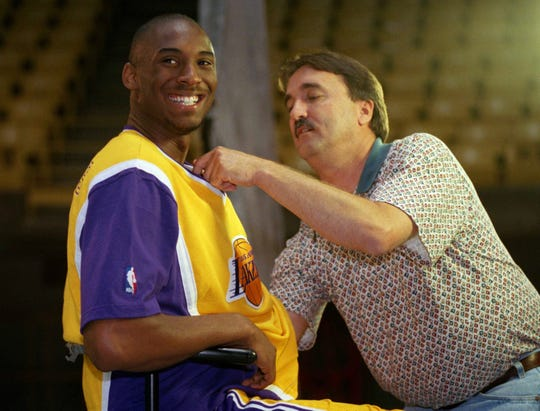 Los Angeles Lakers rookie Kobe Bryant is heckled by teammates as a television cameraman adjusts a microphone on his jersey for an interviewed during the Lakers' Media Day at the Forum in Inglewood, California on Monday, Oct. 14, 1996.