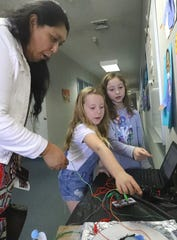 Louisa Guest, left, learns about the Money Machine that was invented by Sycamore Elementary School students Tenley Owens, center, and Taylor Price in their Spanish dual immersion class.