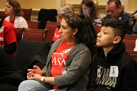A woman and a young man listen to testimony on three immigration bills that would change how the state of Maryland deals with immigration and immigration enforcement by the federal government on Feb. 26, 2020 in Annapolis.