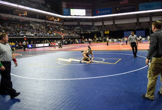 Wrestlers face off during the state wrestling tournament on Thursday, Feb. 27, 2020 at the Premier Center.