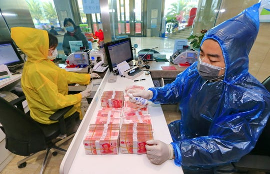 A bank clerk disinfects banknotes in the headquarters of the Suining Bank in Suining city in southwest China's Sichuan province Wednesday. China's central bank has ordered banks to ensure the safety of the cash circulation through putting money through quarantine period or disinfection and destroying cash from places like hospital and public transport services to curb the spread of the coronavirus.