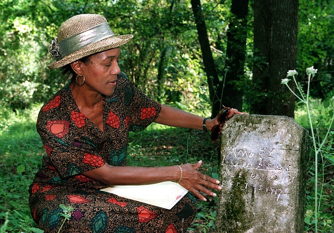 Althemese Barnes looks at the grave of her step great-grandmother who was buried in the old plantation cemetery. The cemetery is located on a woodsy under-growth laden piece of property on Betton Road.