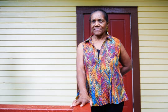 Althemese Barnes, founding director of the Riley Foundation, stands outside of the Riley House.