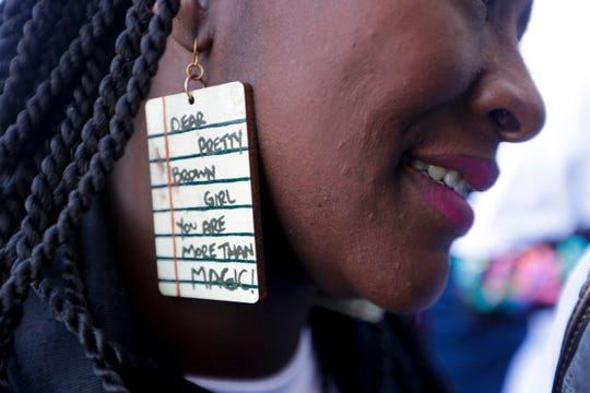 """A woman wears earrings reading """"Dear pretty brown girl you are more than MAGIC!"""" as she enters the Capitol with a group of around 150 black women and girls for Black Girls Day Thursday, Feb. 27, 2020."""