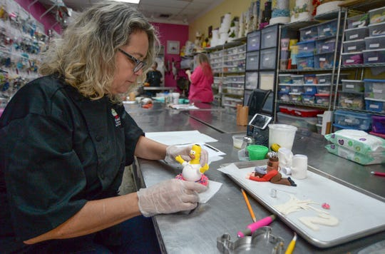 Virginia Prado, assistant cake artist at The Cake Lady, creates a decoration of Homer Simpson for a customer's cake on Wednesday, Feb. 26, 2020, in their kitchen in Downtown Fort Pierce.    CQ: Virginia Prado
