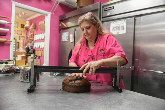 """Staci Dunn, owner of The Cake Lady, works on cutting layers for a cake inside the kitchen of her bakery on Wednesday, Feb. 26, 2020, in downtown Fort Pierce. Dunn is being featured on the Food Network in a competition called """"The Big Bake"""" TV show, to air sometime in March or April. """"That was so much fun, being on a TV show is very exciting. It was confirmation that we're doing a good job, making people happy,"""" Dunn said. """"Being recognized in the industry is just phenomenal. Being one in 54 teams across the world is pretty exciting."""""""