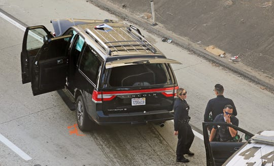 Los Angeles police officers stand after a pursuit of a stolen hearse with with a casket and body inside on Interstate 110 on Thursday.  The hearse was stolen from outside a Greek Orthodox church in East Pasadena on Wednesday night.