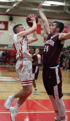 Tappan Zee's Connor Maloney shoots under pressure from Harrison's Michael Plotkin during their playoff game at Tappan Zee Feb. 26, 2020. Tappan Zee won 67-42.