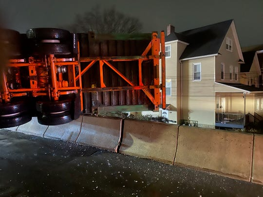 The overturned trailer hung over a residential neighborhood.
