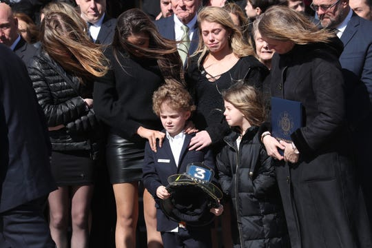 Thomas (T.J.) Foley, 6,  holds his father's firefighter helmet as he stands with the rest of his family outside Holy Family Church in New Rochelle following his funeral mass Feb. 27, 2020. Foley, who joined the FDNY in 1998 and served in Rescue Co. 3 in the Bronx, died on Saturday at the age of 46 after suffering from 9/11-related pancreatic cancer tj 6, carrie,