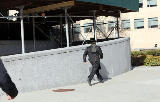 Rabbi Yehuda Oshry runs from reporters after leaving United States District Court in White Plains Feb. 27, 2020.