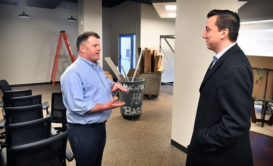 Henry Florsheim, left, president of the Wichita Falls Chamber of Commerce, talks with Cody Magana of White Realty Management about the chamber moving into new office space on the first floor of the Hamilton Building.