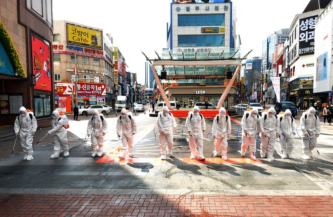 South Korean army soldiers wearing protective suits spray disinfectant to prevent the spread of the COVID-19 virus on a street in Daegu, South Korea, Feb. 27, 2020. As the worst-hit areas of Asia continued to struggle with a viral epidemic, with hundreds more cases reported Thursday in South Korea and China, worries about infection and containment spread across the globe.