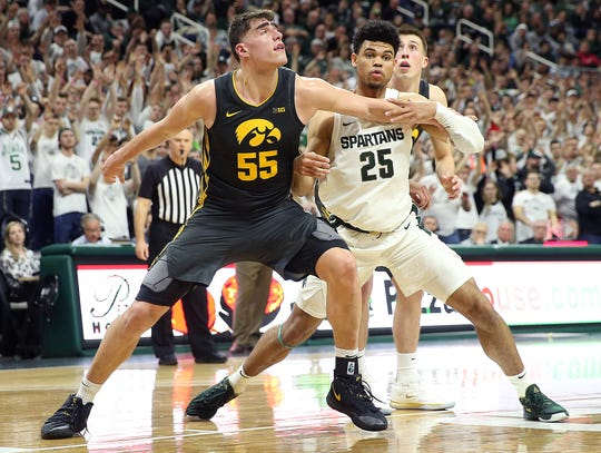 Iowa center Luka Garza (55) and Michigan State forward Malik Hall fight for position during the second half of their game at the Breslin Center.