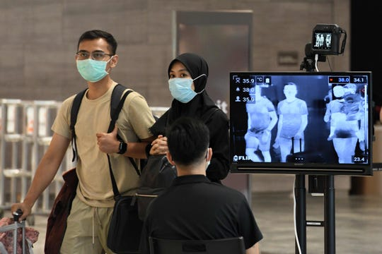A couple, wearing protective masks amid fears about the spread of the COVID-19 novel coronavirus, walk past a temperature screening check at Changi International Airport in Singapore on Feb. 27, 2020.