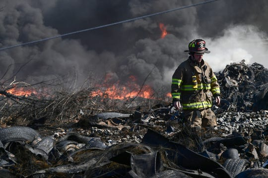 Bud Callaham of Broadway fire looks walks by flames at a working tire fire at Viva Recycling of South Carolina on S.C. 28 South in Anderson Friday morning.