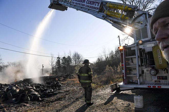 Anderson County firemen spray from  a ladder truck, working a tire fire at Viva Recycling of South Carolina on S.C. 28 South in Anderson Friday morning.