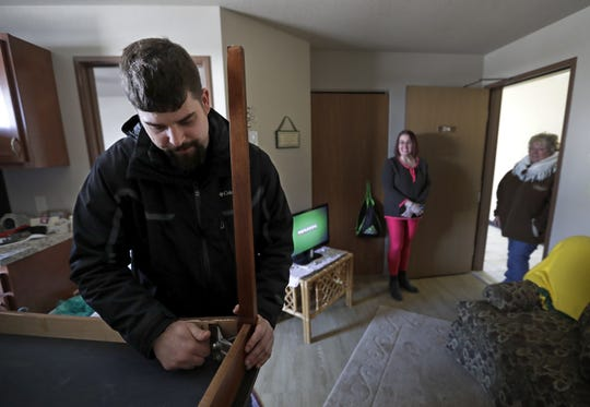 Josh Andreini, left, Navigator for Wisconsin Veterans Village Association assembles a donated table for Angel Moore in her apartment at the village on Feb. 21, 2020 in Appleton.