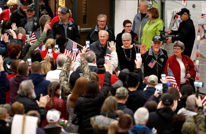 Vietnam veterans who participated in the Old Glory Honor Flight Return to Vietnam are greeted during a reception at Menasha High School in 2019.