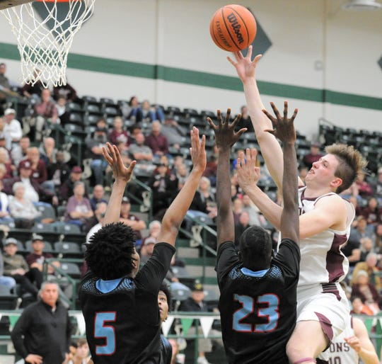 Brownwood senior Zach Strong goes for a shot in the lane as Hirschi's Kiove Nielson (23) and Jaeden Whitten (5) defend in a Region I-4A area playoff Thursday, Feb. 27, 2020, at the Breckenridge ISD Athletic and Fine Arts Center.