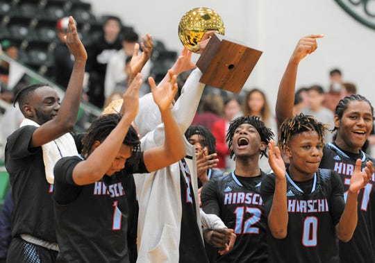 Members of the Wichita Falls Hirschi boys basketball team celebrate with their trophy following a win over Brownwood in a Region I-4A area playoff Thursday, Feb. 27, 2020, at the Breckenridge ISD Athletic and Fine Arts Center.