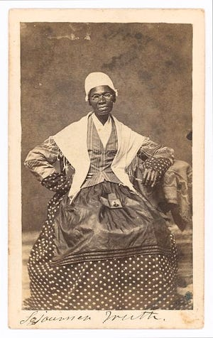 Sojourner Truth seated with photograph of her grandson, James Caldwell of Co. H, 54th Massachusetts Infantry Regiment, on her lap.