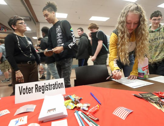 Kyla Anderson, 17, right, registers to vote at Bremerton High School on Feb. 28.