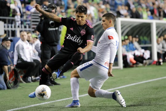 Seattle Sounders forward Raul Ruidiaz, left, tries to keep the ball in play as Olimpia defender Johnny Leveron, right, closes in during the first half of a CONCACAF Champions League soccer match Thursday. Seattle lost the series and will open MLS play Sunday against Chicago.